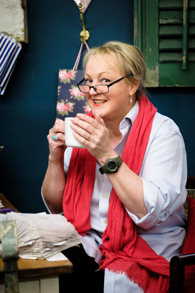 Personal Branding Photography with Number Ten Interiors - owner wearing bright red scarf taking a coffee break