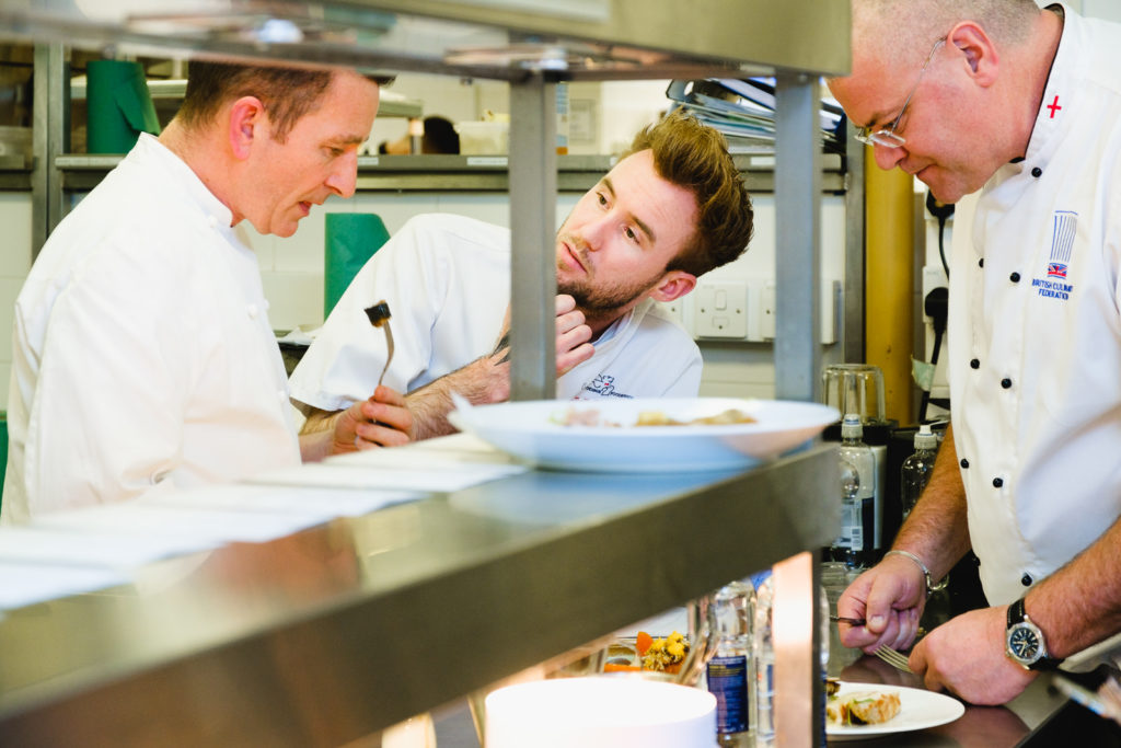 Corporate marketing photography with judges tasting dishes at Chef vs Chef competition