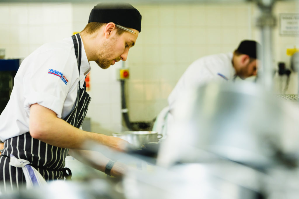 Corporate marketing photography with chefs preparing dishes at Chef vs Chef competition