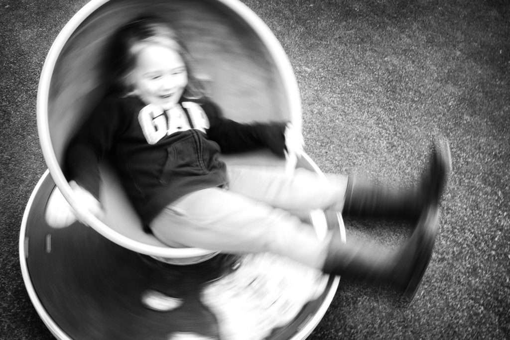 Black and white family photography with young girl spinning on roundabout with blurred motion