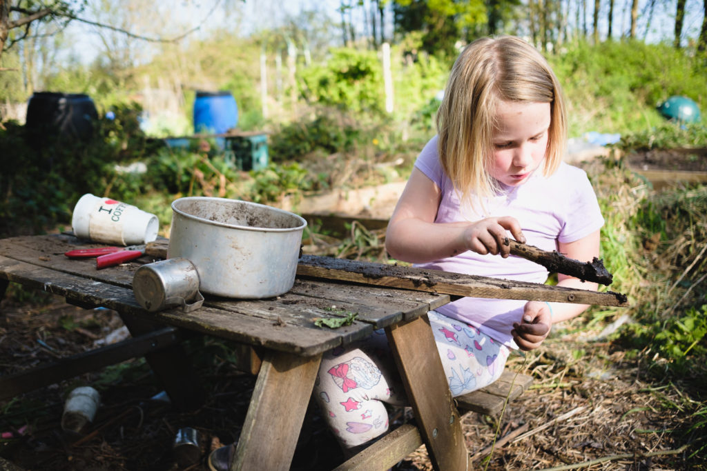Family photography - young girl playing with sticks and mud at the allotment