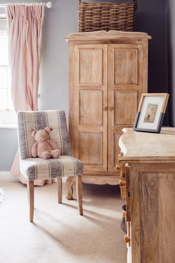 Corporate marketing photography with simply designed girls bedroom with wooden furniture and pastel colours