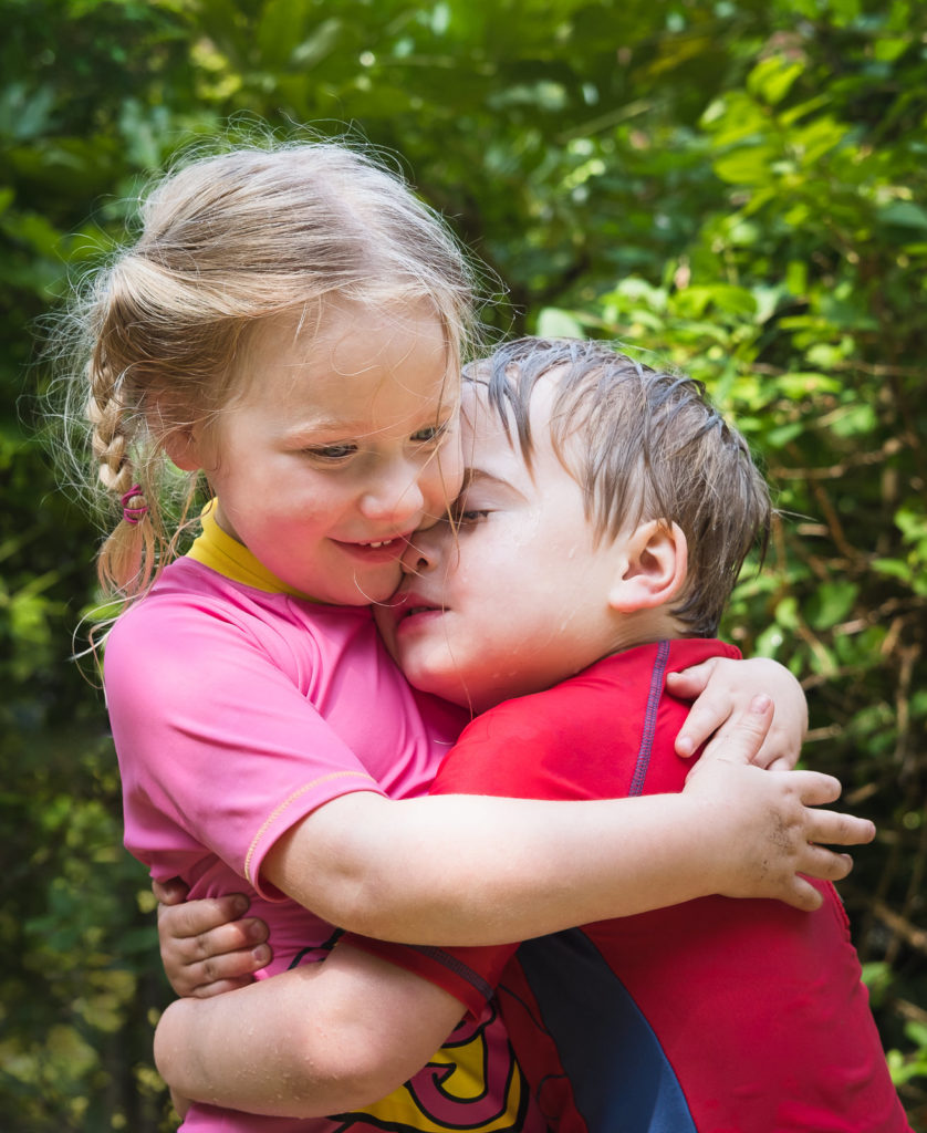 Family photography with young brother and sister wearing bright UV suits in loving hug