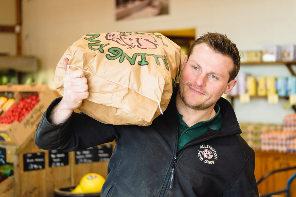 Corporate marketing photography with farm shop manager carrying sack of potatoes at Allington Farm shop in Wiltshire