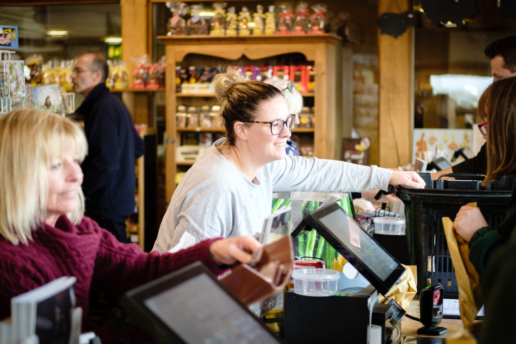Corporate marketing photography with customer talking to staff on the tills at Allington Farm Shop in Wiltshire