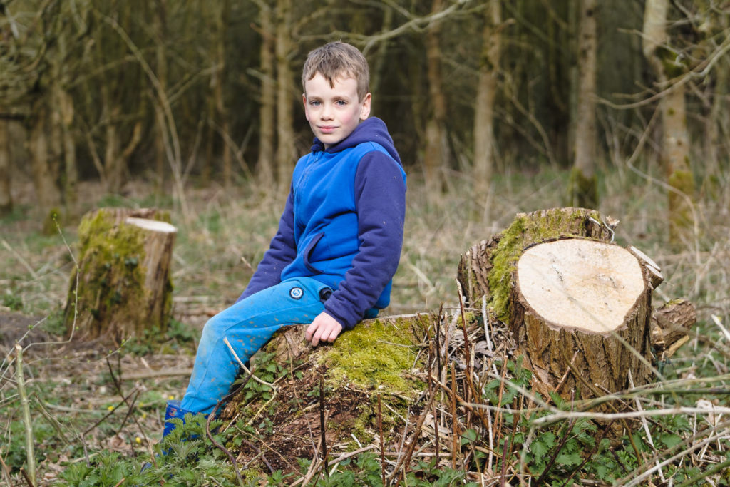 Family photography young boy relaxing on country walk through woods
