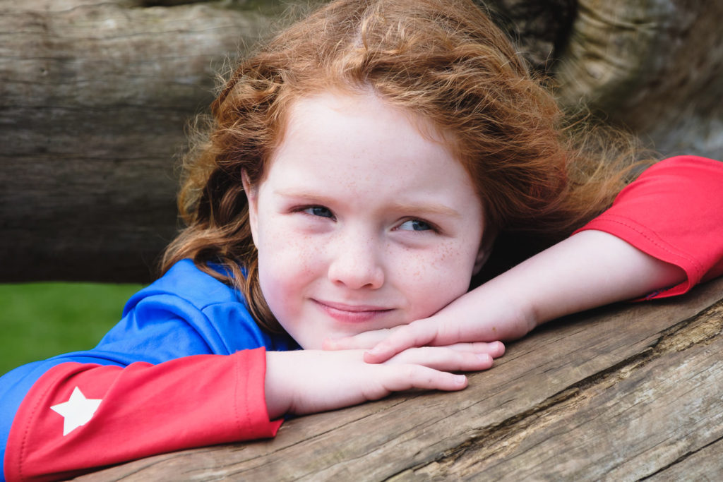 Family photography - portrait of young girl with red hair wearing superhero outfit