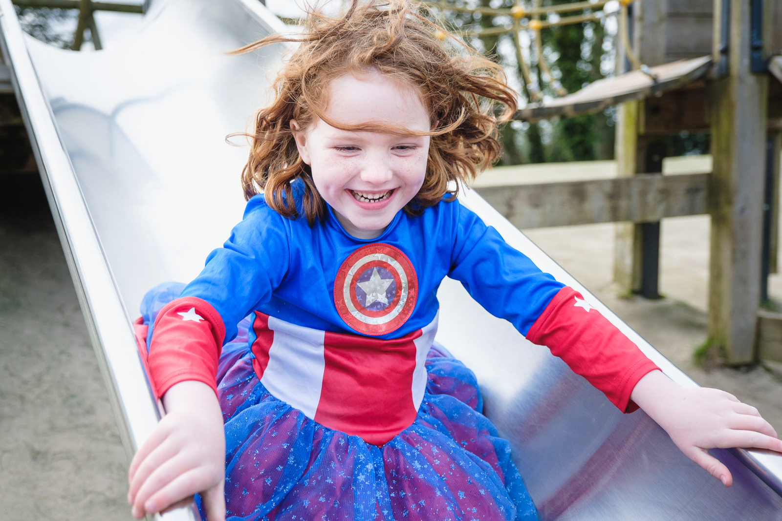 Family photography - portrait of young girl enjoying a slide in Bristol park wearing superhero outfit