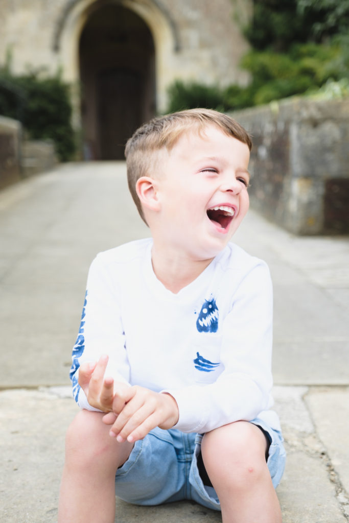 Family photography - young boy relaxed and laughing outside Wiltshire church