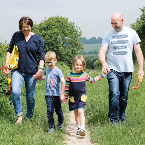 Keri with her family, all holding hands on a country day out in north Wiltshire