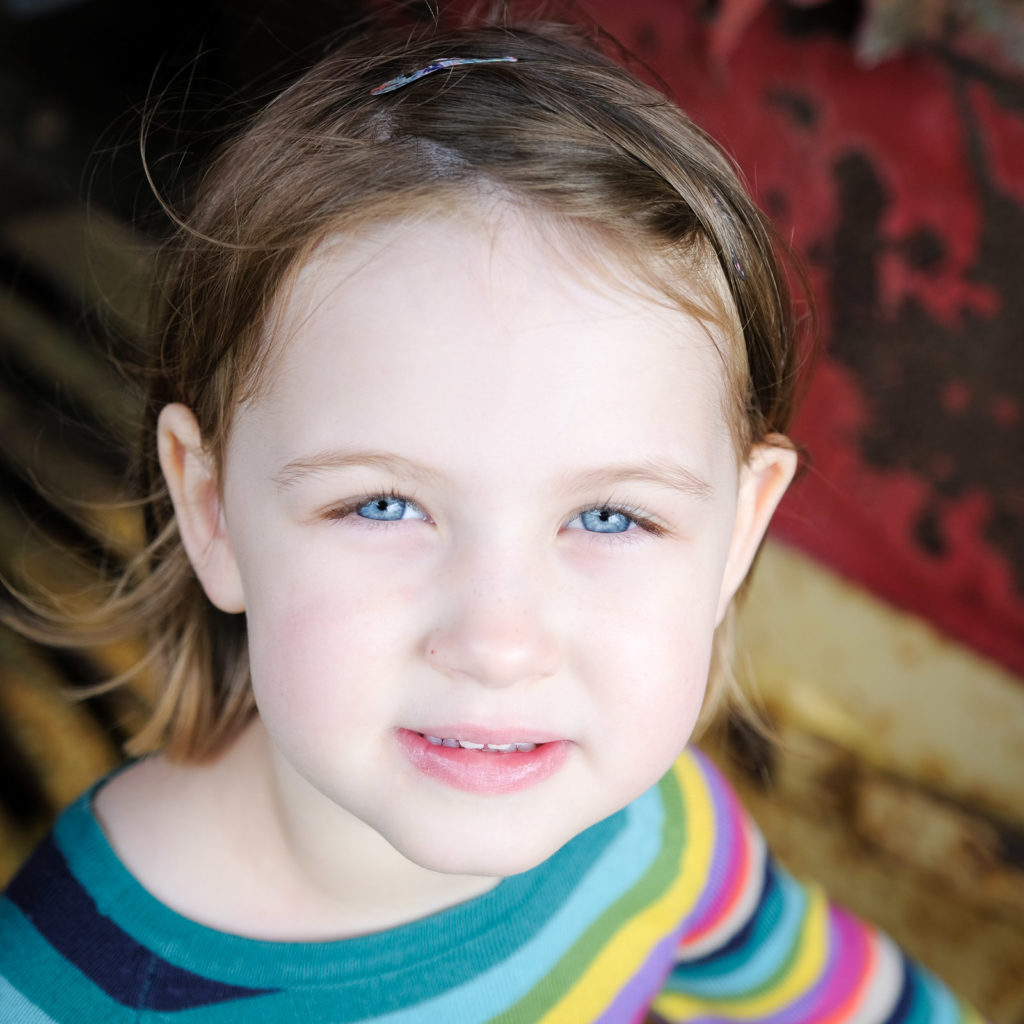 Family photography with a young girl in rainbow striped top and blue eyes