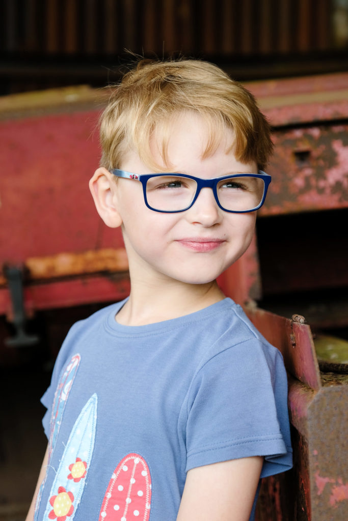 Family photography with a boy in cool glasses looking into the distance
