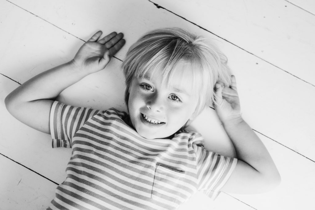 Home photo session - black and white photo of boy lying down on painted white floorboards