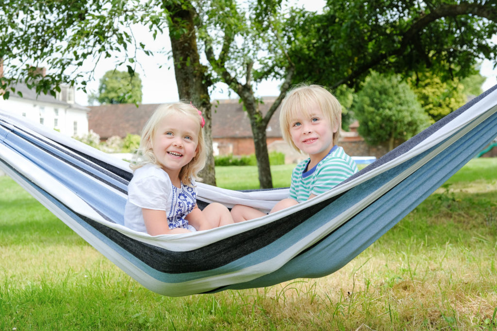 Family photography with young brother and sister playing in hammock in back garden