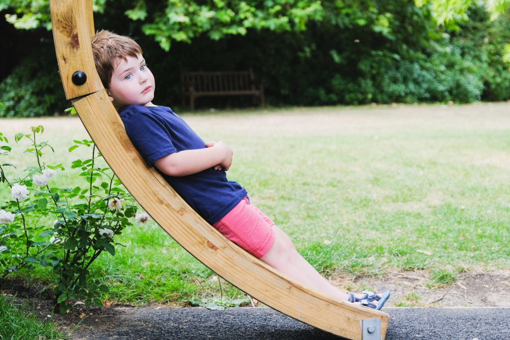 Family photo session with young boy relaxing on wooden arch at Bath Botanical Gardens