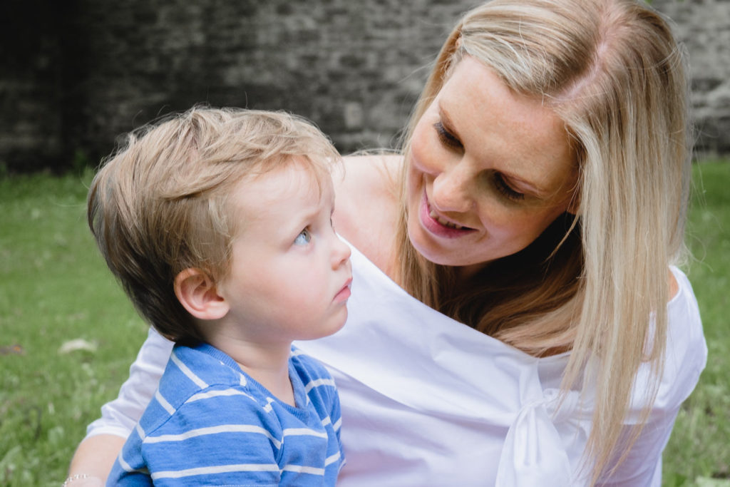 Family photography with mum cuddling son in the grounds of Corsham Court