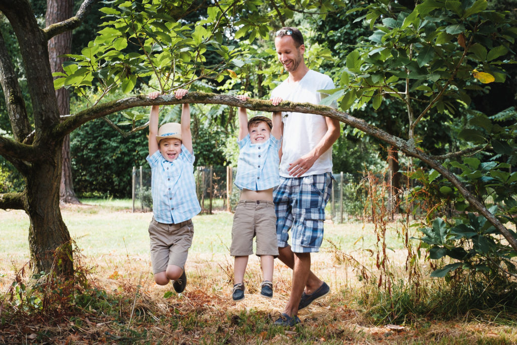 Family photography - dad playing with young boys on hot summer day at Westonbirt Arboretum