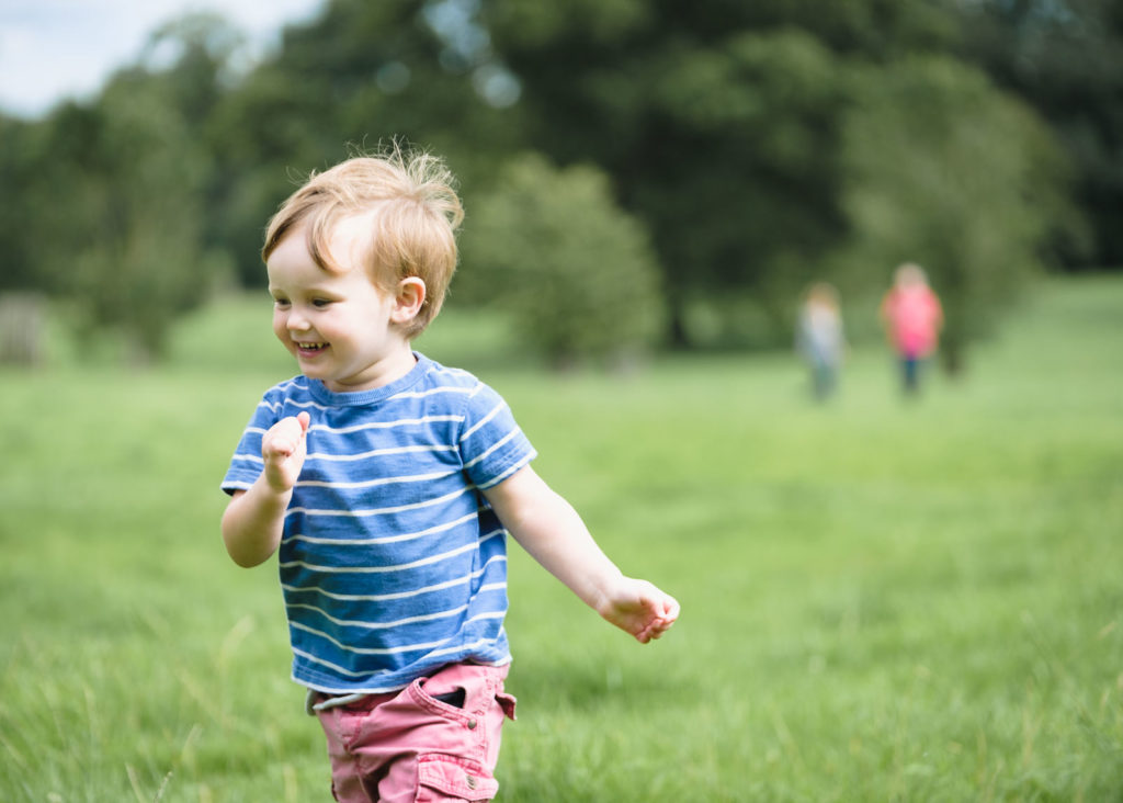 Family photography with young boy running care free in field at Corsham Court in Wiltshire