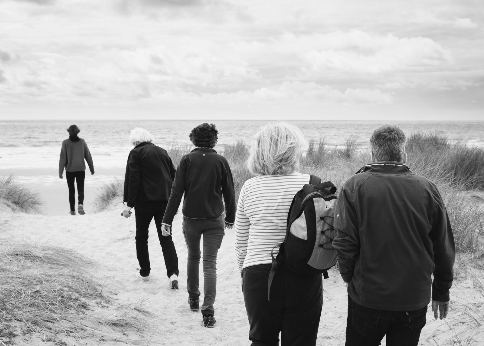 Black and white family photography with family heading through dunes on beach walk