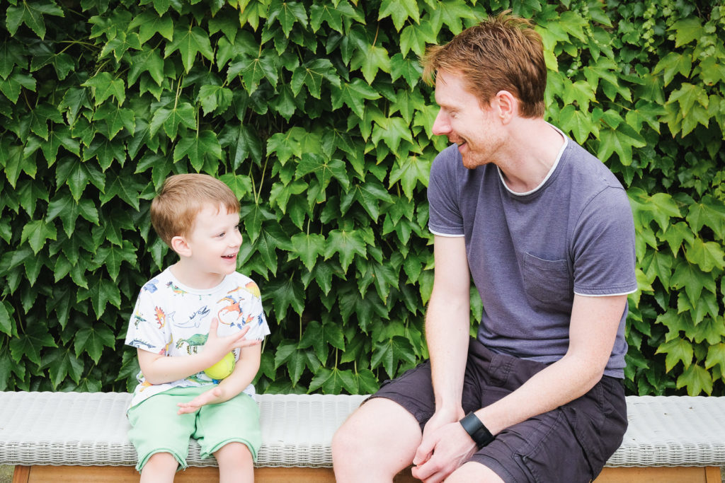Family photography - dad and young son chatting in the garden at Cotswold county house