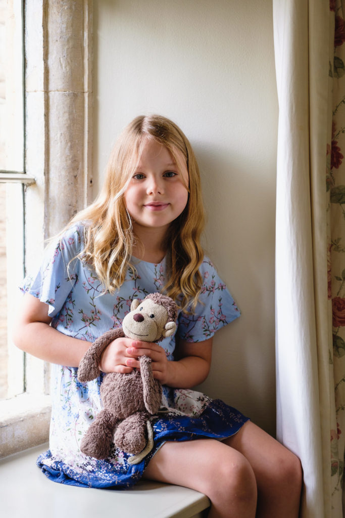 Family photography with young girl and her favourite toy in Cotswold county house