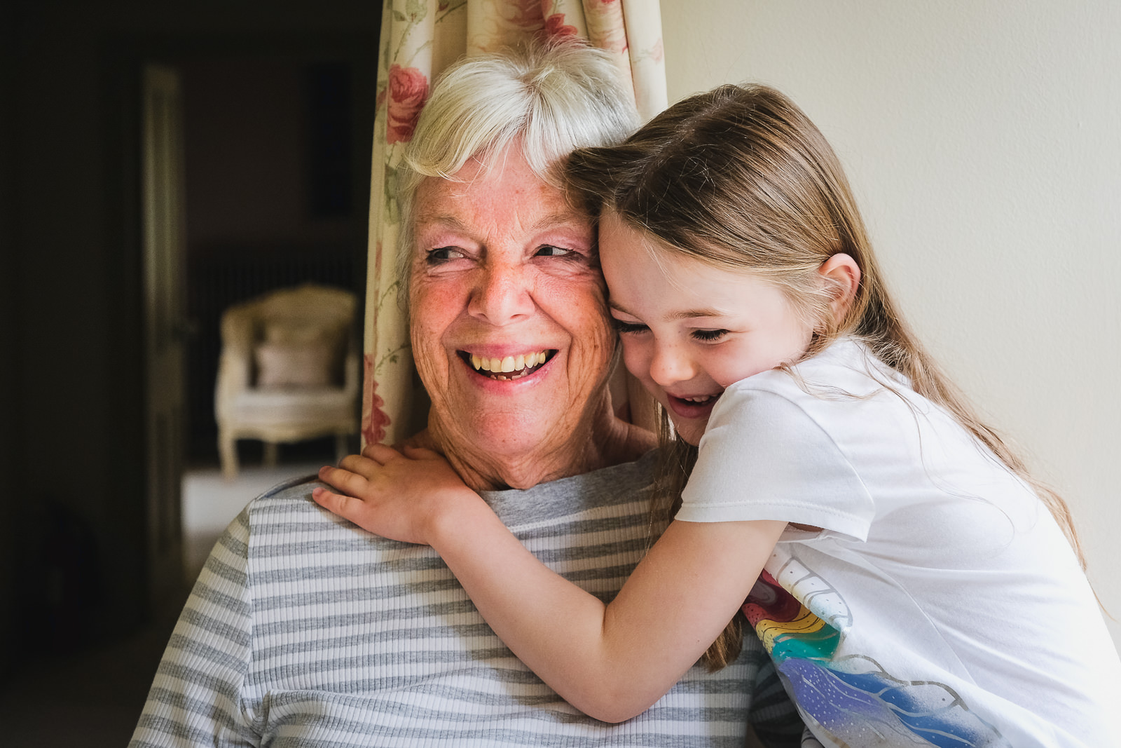 Special occasion family photography - grandmother and granddaughter smiling and cuddling at family celebration