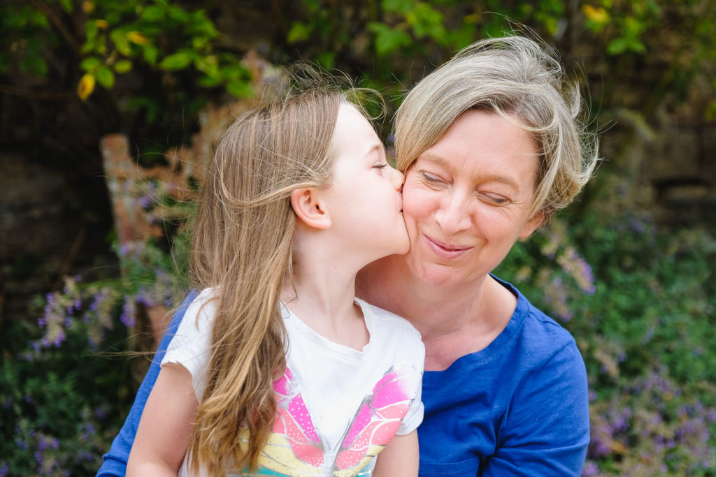 Family holiday photography - young girl kissing her mum in Cotswold country garden