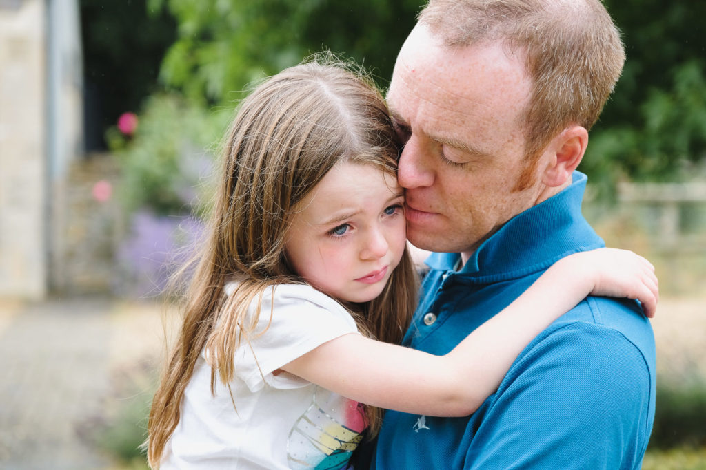 Family holiday photography - young tearful girl hugging dad in Cotswold county house gardens