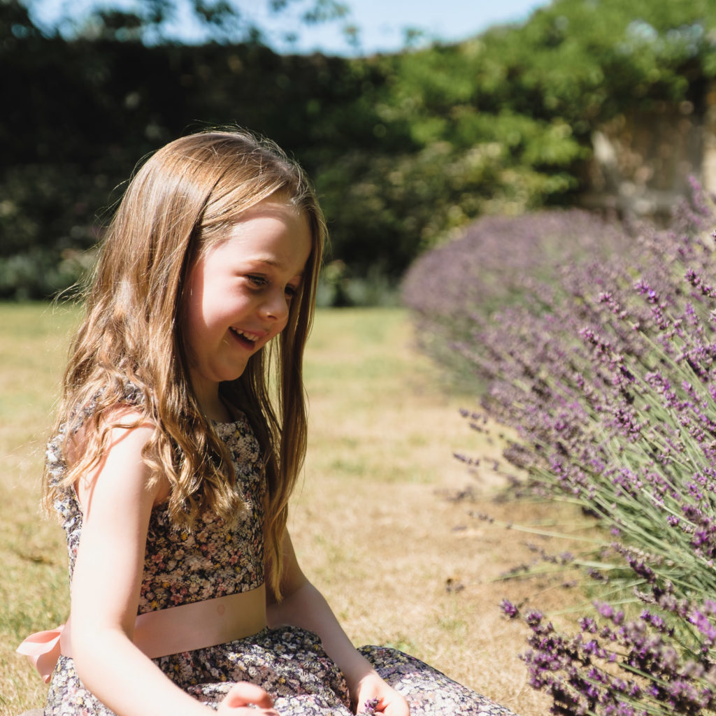 Family holiday photography - young girl in floral dress with lavender at Cotswold county house