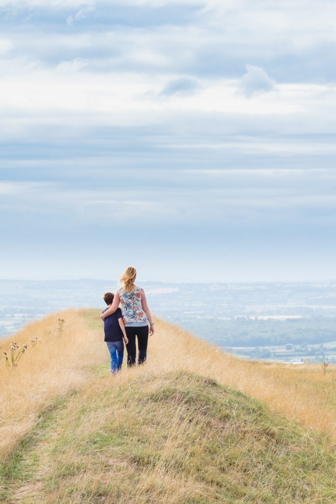 Family photography - mum and son hugging and enjoying view at Westbury white horse