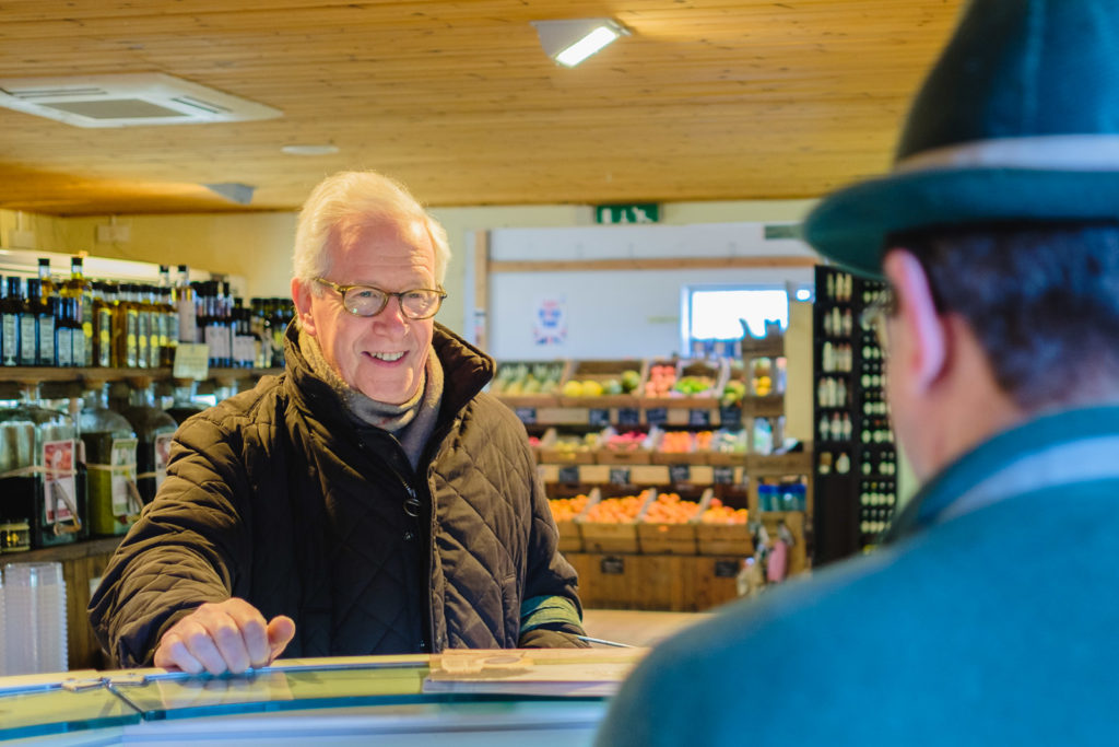 Corporate marketing photography with customer talking to staff on the deli counter at Allington Farm Shop in Wiltshire