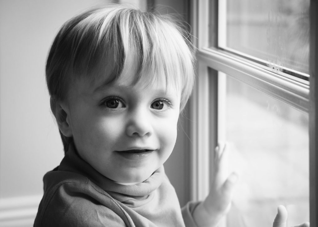Black and white family photography with young boy in front of window
