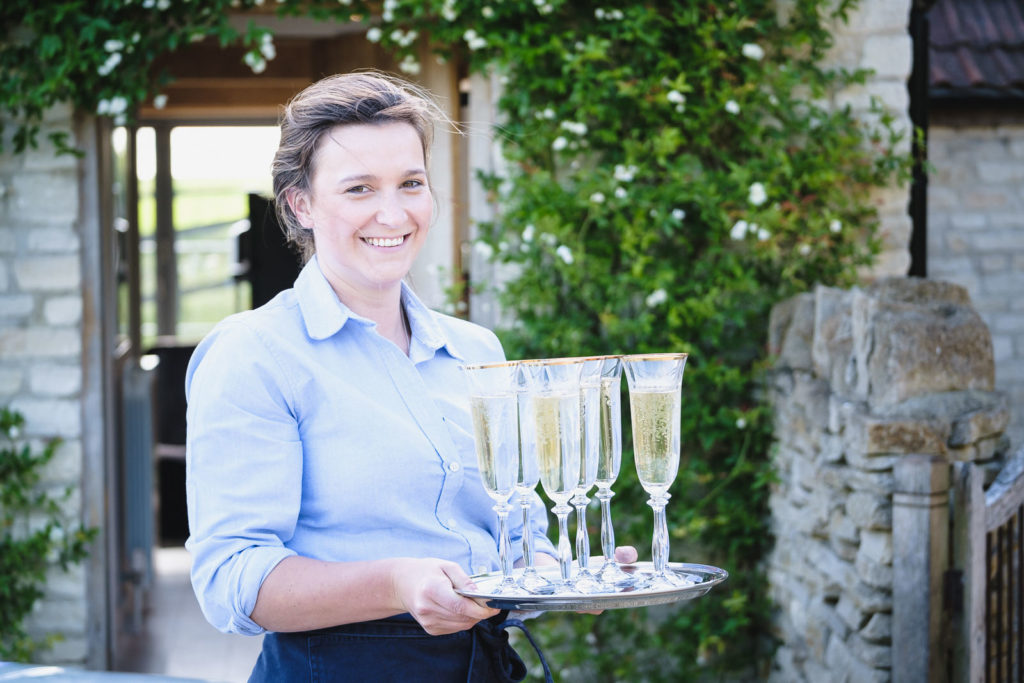 Corporate event photography with waitress ready to serve champagne to guests