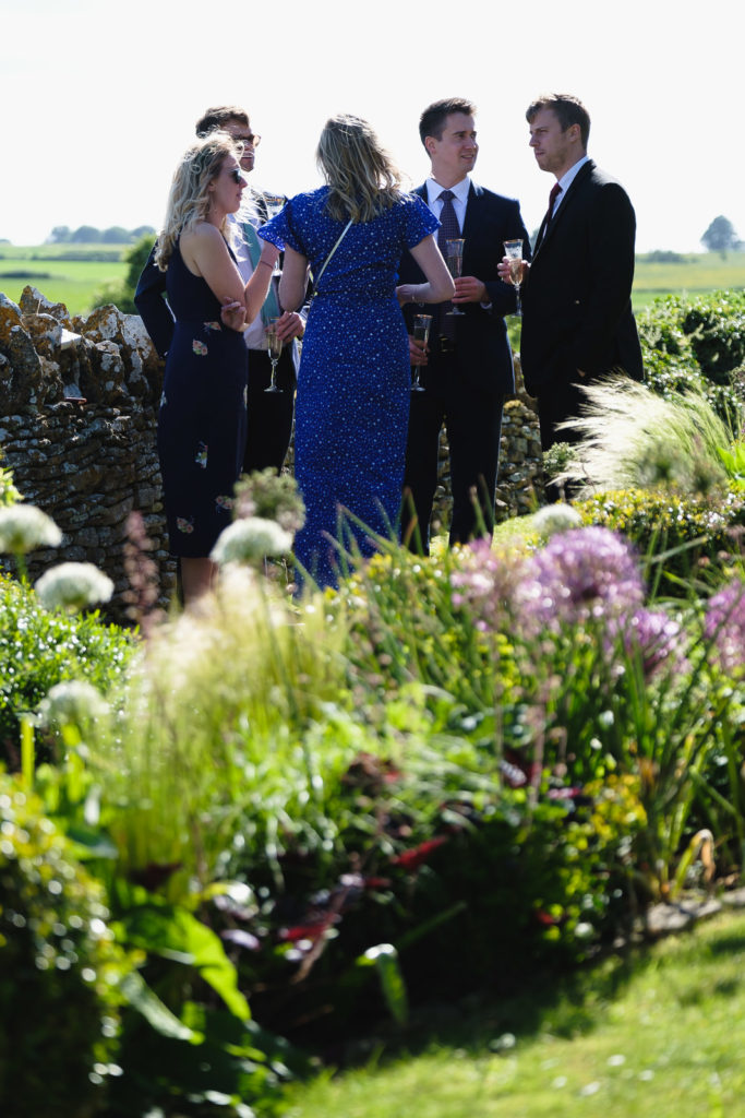 Wedding photography with guests enjoying a drink in a summer garden