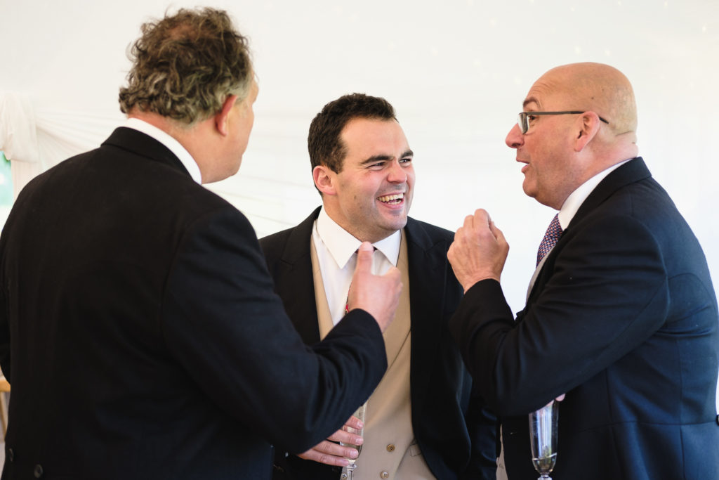 Wedding photography with three men laughing and joking