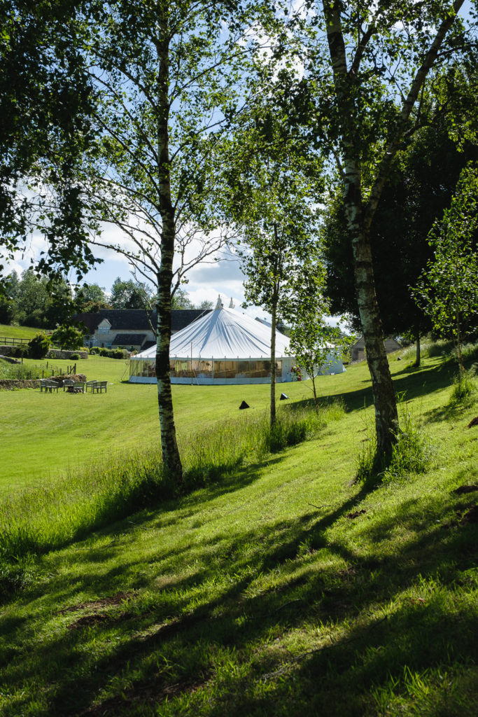 Wedding photography with view of marquee through trees in rolling Cotswold countryside