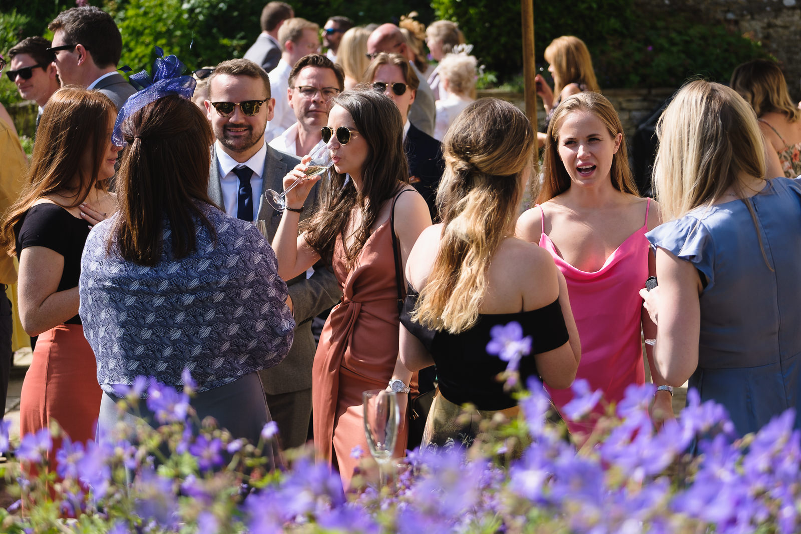 Wedding photography with guests enjoying conversation and drinks on hot English summer day at English country wedding