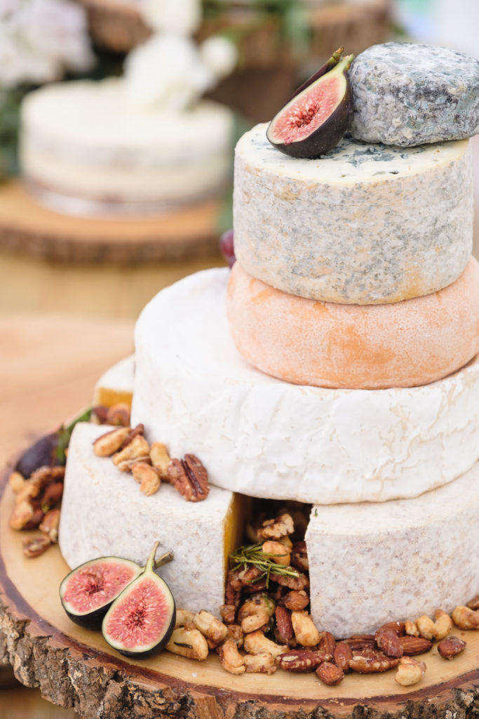 Wedding photography of whole cheeses with figs and nuts at English country wedding