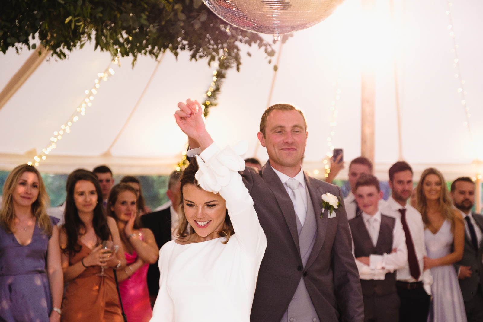 Wedding photography with first dance under glitter ball in beautifully lit marquee