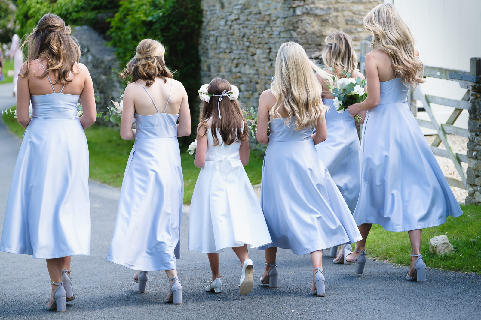 Wedding photography with bridesmaids wearing blue silk dresses walking to the church