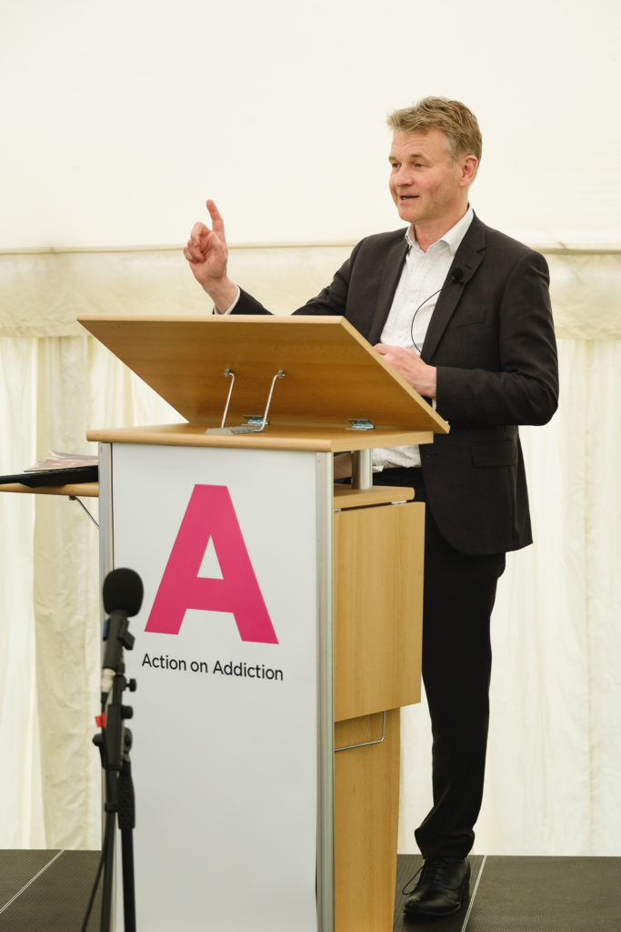 Corporate event photography with chief executive of charity Action on Addiction (Graham Beech) making a presentation at a conference