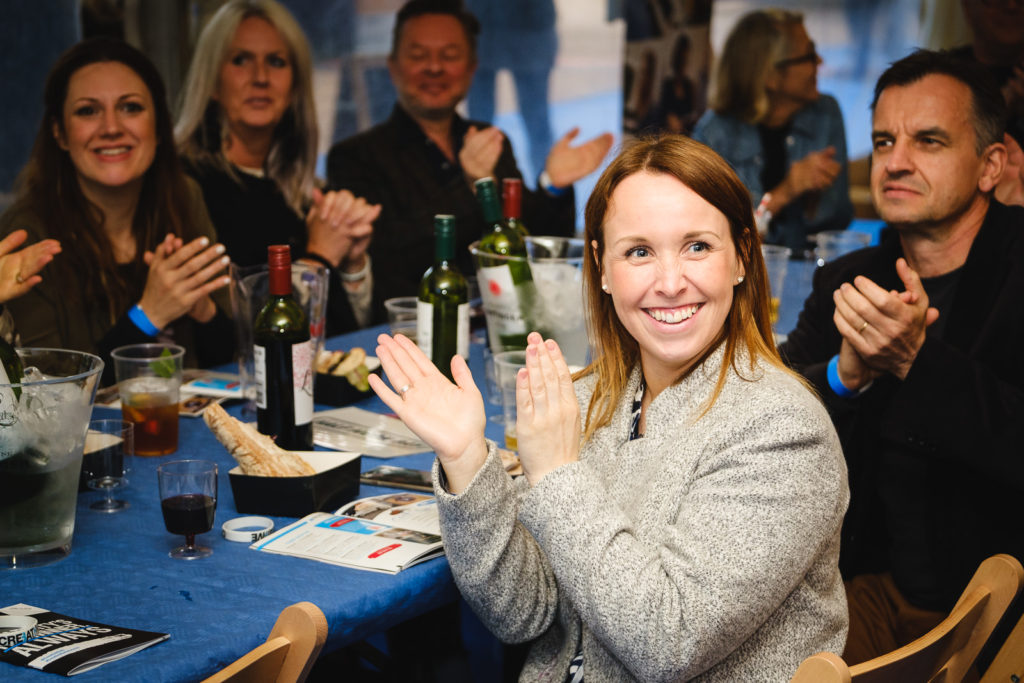 Corporate event photography at Bath Creative Awards with female guest enjoying prize giving ceremony
