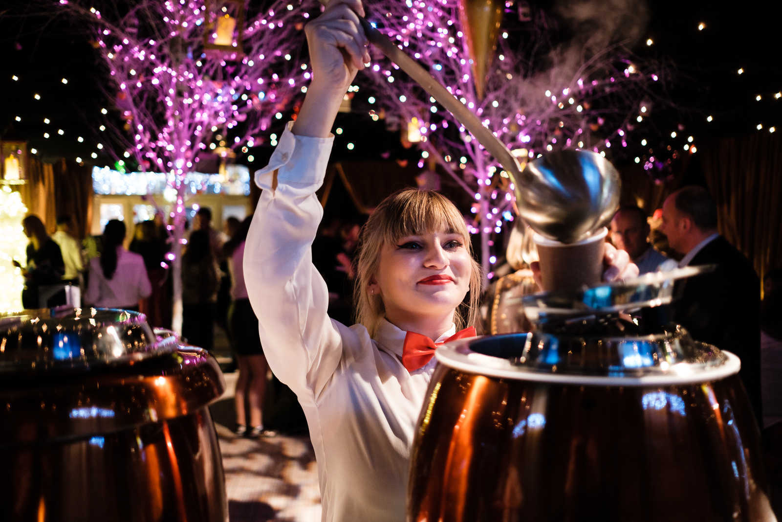 Corporate event photography with Christmas decorations and Waitress serving mulled wine