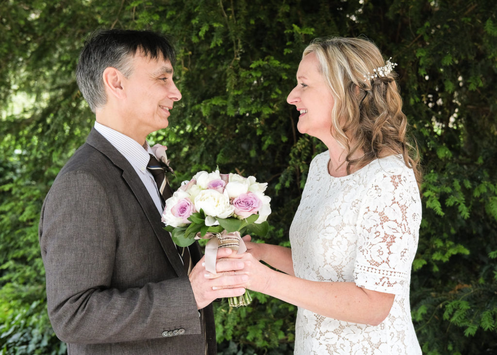 Wedding photography with bride and groom holding bouquet and looking at each other lovingly