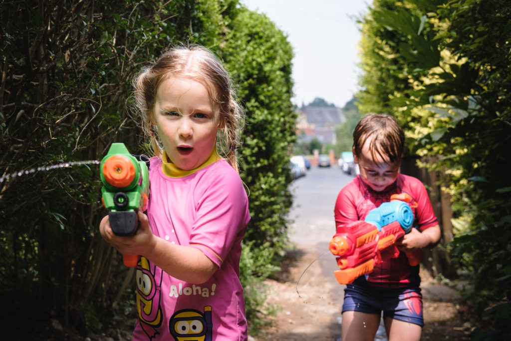 Family photography with two kids excitedly playing with water pistols, turning on the photographer