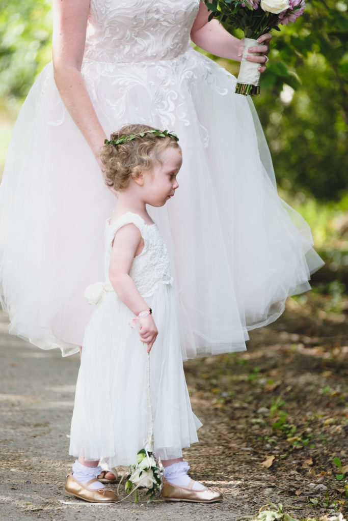 Wedding photography - bride and young daughter walking along lane before wedding ceremony