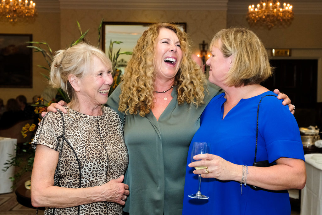 Corporate event photography with three ladies sharing a funny story at Lucknam Park Wiltshire