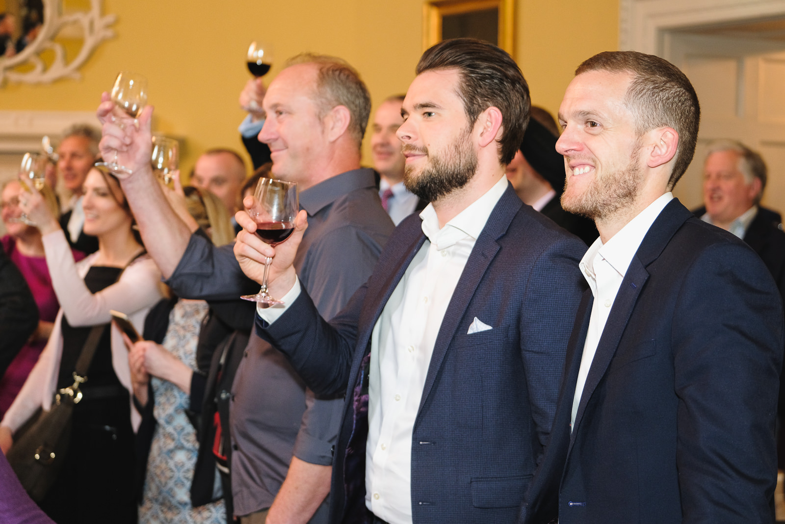 Corporate event photography with group raising a toast to the speaker at the Bath Assembly Rooms