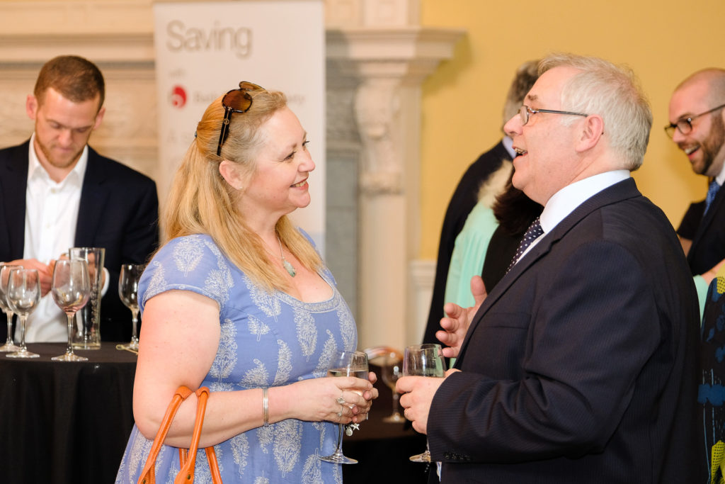 Corporate event photography with lady talking to chief exec at the Bath Assembly rooms