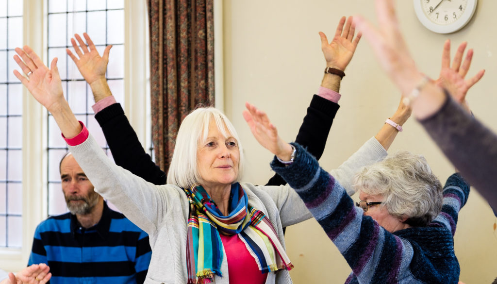 Commercial event photography with group enjoying warm up at choir group in Bath
